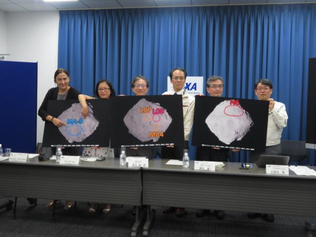 着陸候補地を示すポスターの前に並んだプロジェクトメンバー